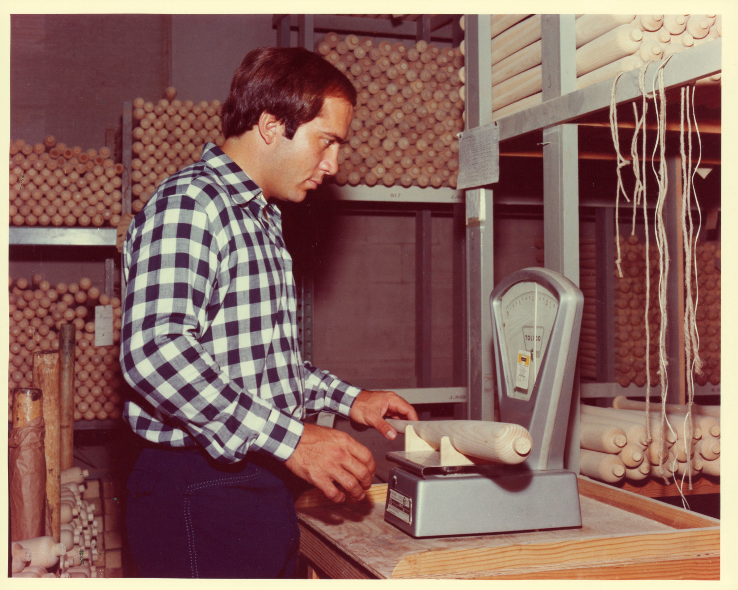 Johnny Bench weighing one of his bats during a trip to the factory.